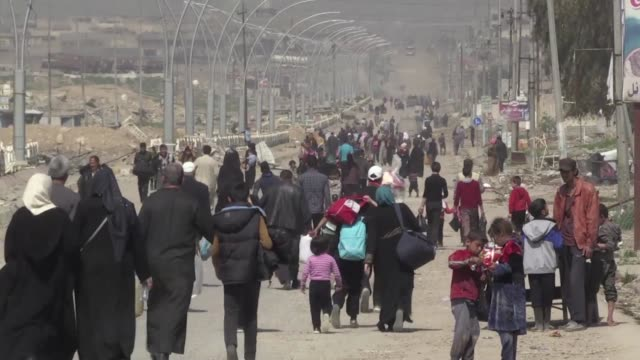 On west Mosul's Baghdad street thousands of displaced Iraqis flee the fighting with their meagre belongings but similar numbers walk in the other...