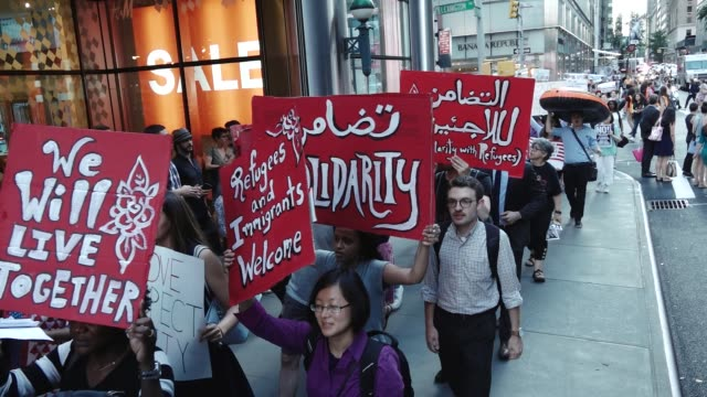 On World Refugee Day a group of protestors gathered on Manhattan's 59th Street % 5th Avenue to protest the United States President's policies and...
