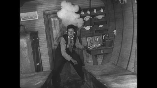1921 onboard small boat during storm, man (buster keaton) attempts to use radio to call for help - 1921 stock videos & royalty-free footage