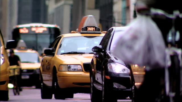 Oncoming traffic two taxi cabs black car unidentifiable man on bicycle moving toward camera on busy street RACK FOCUS to yellow taxi cab bus moving...