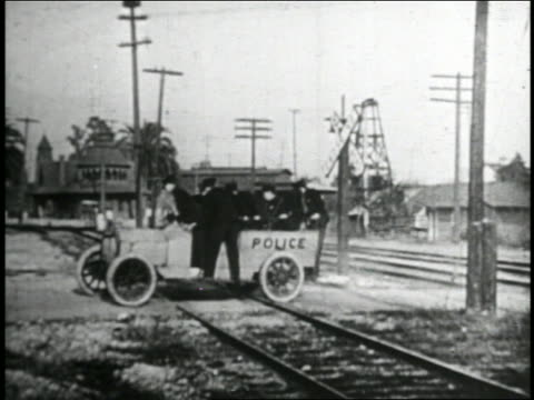b/w 1935 oncoming train smashing into keystone kops attempting to free stuck police truck from track - 1935 stock videos & royalty-free footage