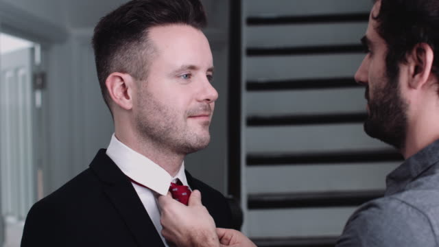 One adult man adjusting tie to his partner