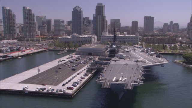 vídeos de stock e filmes b-roll de one america plaza and other san diego skyscrapers tower behind the uss midway aircraft carrier. - uss midway