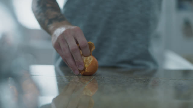 cu one armed man peels an orange with one hand - human finger stock videos & royalty-free footage