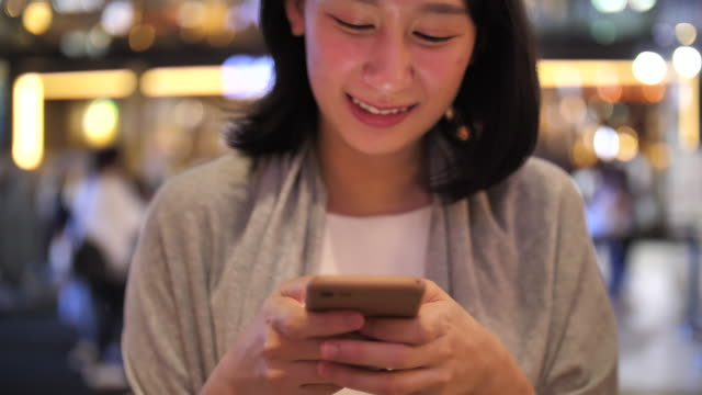 one asia woman texting  with beautiful bokeh background in the city at night - columnist stock videos & royalty-free footage