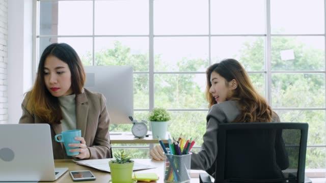 Eine asiatische Geschäftsfrau bewegt sich mit Stuhl zu anoterh Kollegen, um über die Arbeit am Schreibtisch im modernen Büro zu diskutieren