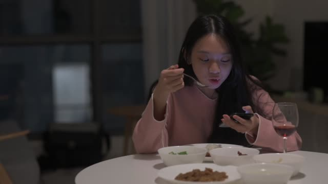 アジアの中国人女性1人が、自分のスマートフォンで赤ワインを楽しんでいるダイニングルームで自宅で夕食を食べている - 孤独点の映像素材/bロール