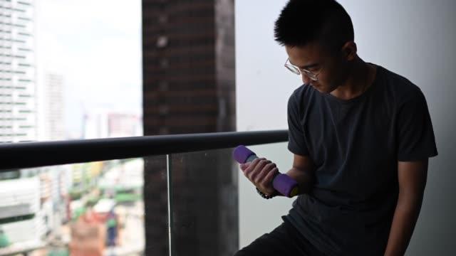 vidéos et rushes de un adolescent chinois asiatique d'entraînement avec sa construction musculaire haltère dans le balcon - 16 17 ans