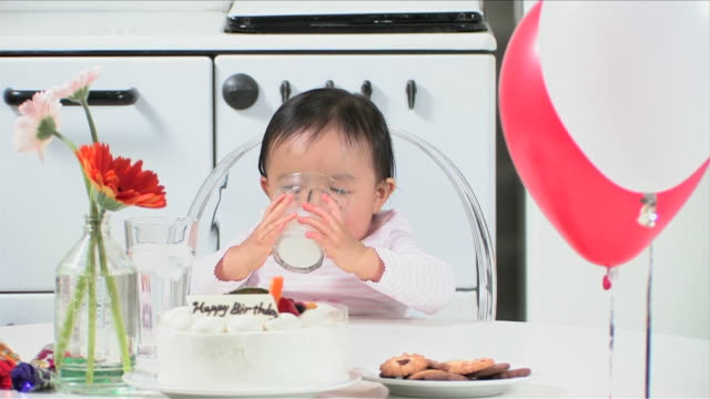 one baby is drinking milk in her birthday party - baby milk stock videos & royalty-free footage