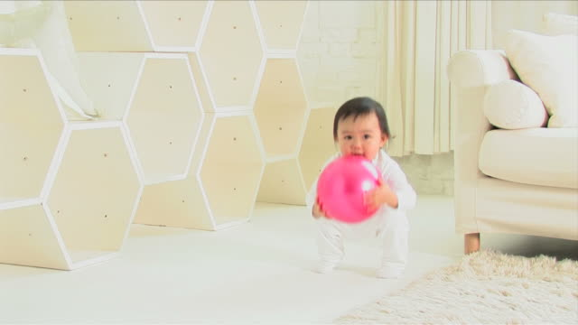 one baby is playing with a ball - ボール点の映像素材/bロール