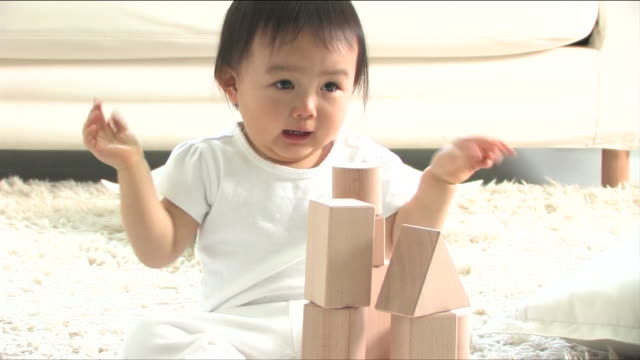 One baby is playing with blocks