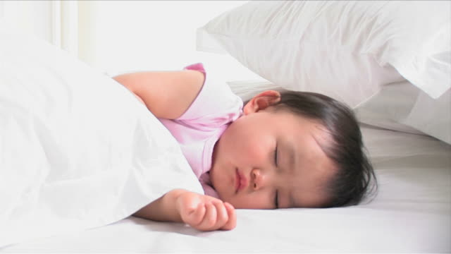 One baby is sleeping on the white bed