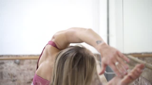 one beautiful woman stretching in front of a mirror. - barre stock videos & royalty-free footage