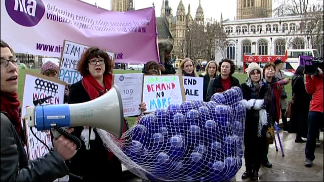 'One Billion Rising' campaign against violence for women flashmob ENGLAND London Parliament Square EXT GVs women holding up signs and others with net...