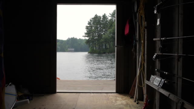 ms one boy going out from boathouse entrance and mother enter in boathouse, another boy come with blue flag in hand / wolfebro, nh, usa  - doorway stock videos & royalty-free footage