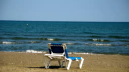 One chaise-longue at perfect wild sandy beach with blue sea view, nobody, travel destinations concept