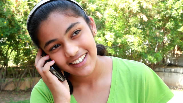 stockvideo's en b-roll-footage met one cheerful casual indian girl talking on the phone - haarband