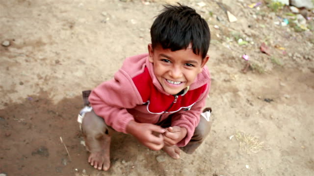 one cheerful rural indian boy looking at camera - poverty stock videos & royalty-free footage