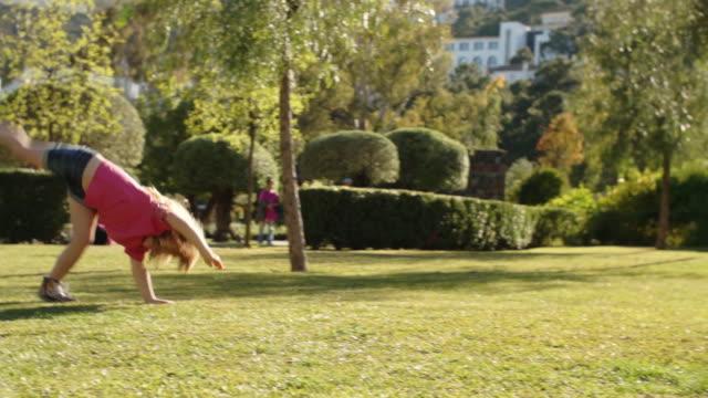 one child doing cartwheels in park. - cartwheel stock videos & royalty-free footage