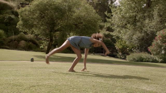 one child doing cartwheels in park - cartwheel stock videos & royalty-free footage