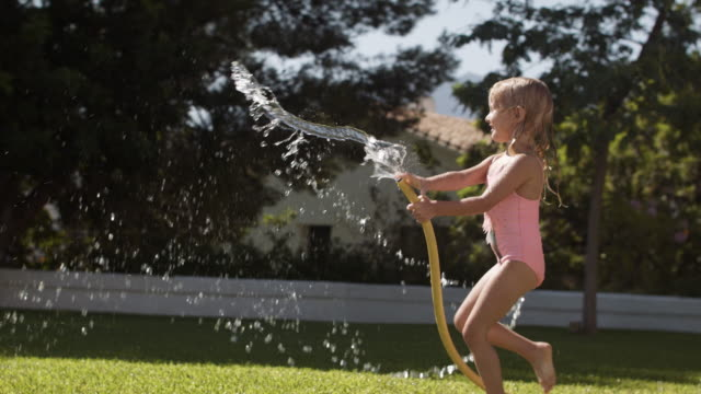 One child playing with water hose in garden