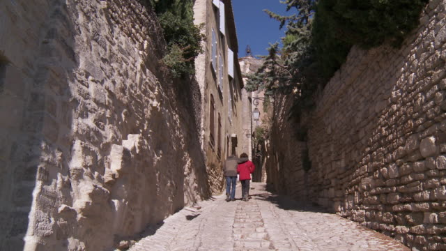 ms one couple walking on stone steps / gordes, vaucluse, france - kopfsteinpflaster stock-videos und b-roll-filmmaterial