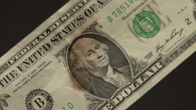 CU U.S. one dollar bill starts to burn up