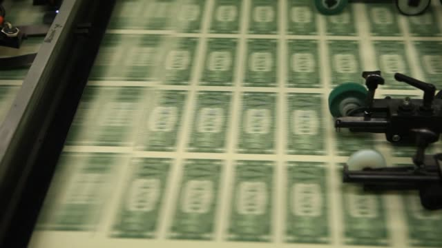 One dollar notes travel through a large examining packaging equipment machine after being banded at the US Bureau of Engraving and Printing in...