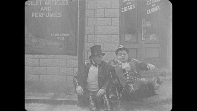 1918 one drunken man (fatty arbuckle) helps another drunken man in rainstorm - drunk stock videos & royalty-free footage