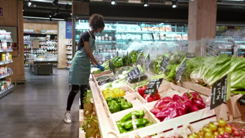 one employee adjusting vegetables at the grocery store. - market retail space stock videos & royalty-free footage