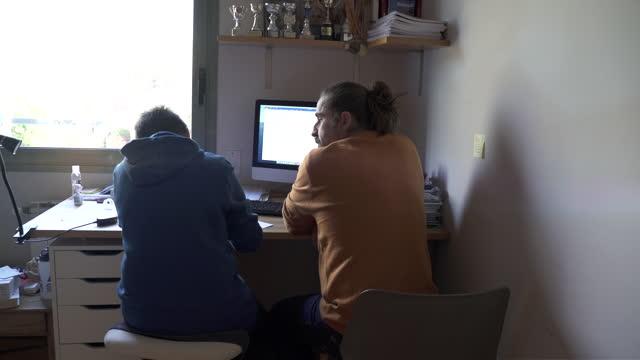 stockvideo's en b-roll-footage met een vader die zijn zoon helpt zijn huiswerk af te maken. - zoon