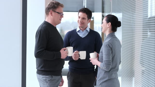 LD One female and two male colleagues chatting over coffee