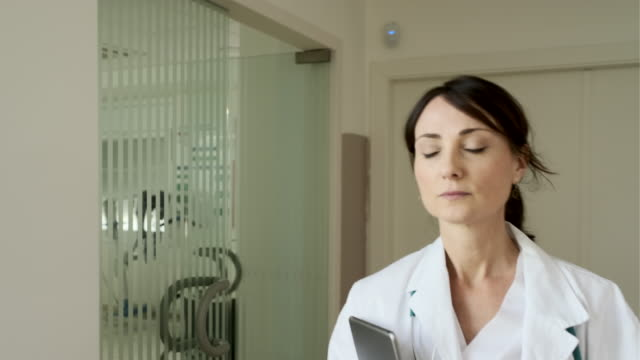 one female doctor walking in the hospital's corridor. - medical occupation stock videos & royalty-free footage