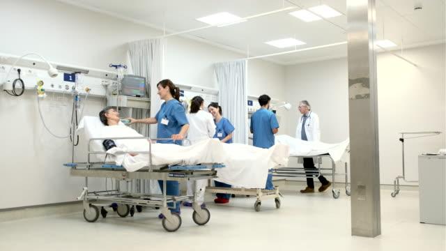 一人の女性看護師が手術後の部屋で患者と話しています。 - 病棟点の映像素材/bロール