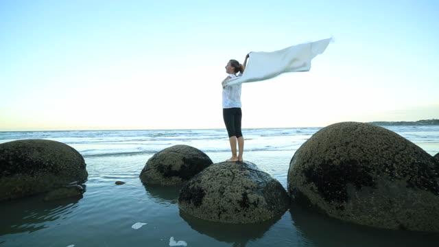 Eine Frau steht auf Felsblock, bietet Decke in der Luft