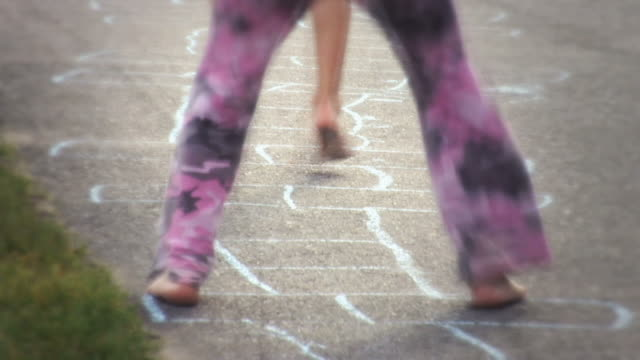 ms  one girl drawing hopscotch with chalk on sidewalk and two girls skip and play hopscotch  / langley, british columbia, canada. - gessetto da lavagna video stock e b–roll