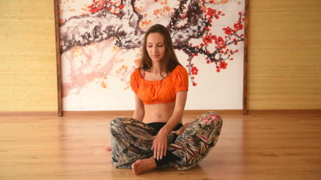 one girl in yoga class meditating in lotus position - lotus position stock videos & royalty-free footage