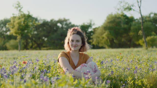 WS SLO MO. One girl sits daydreaming in field of flowers.