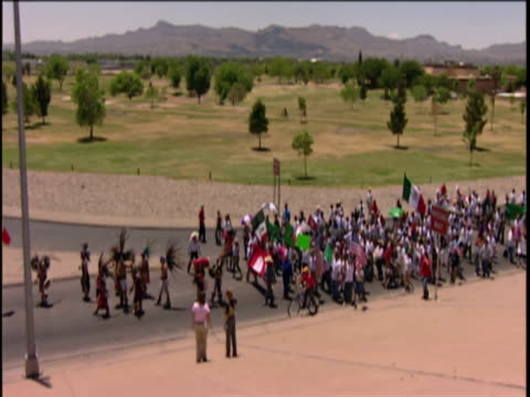 one group of protestors walking down street, other waiting on bridge, el paso, texas, usa - 国境点の映像素材/bロール