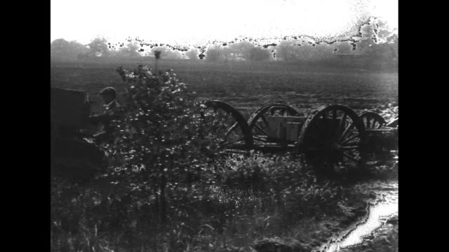one holt caterpillar tractor pulls several caissons across field and through stream and mud / note: exact day/month not known; film has nitrate... - キャタピラー社点の映像素材/bロール