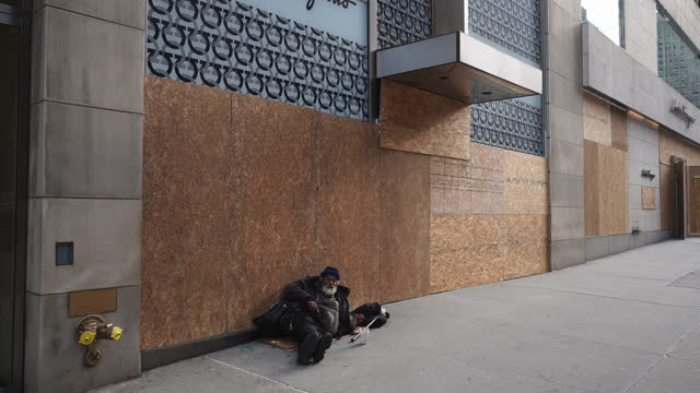 one homeless man lays down on the sidewalk beside the boarded up stores fronts in midtown manhattan. - males stock videos & royalty-free footage