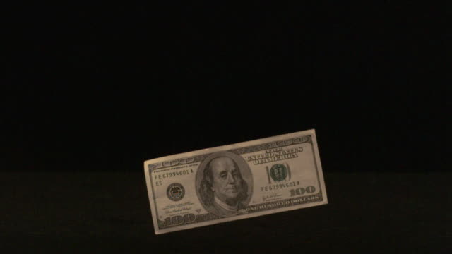 One hundred dollar bill falling through the air (slow motion)