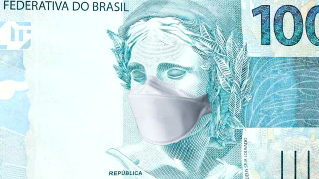 one hundred reais bill with disposable medical mask. concept of the coronavirus epidemic in brazil. impact of the coronavirus pandemic on the brazilian economy - number 100 stock videos & royalty-free footage