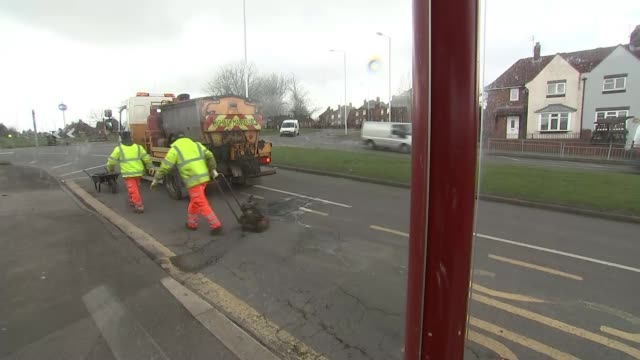One in five roads urgently need repair as councils lack money to fix potholes ENGLAND Yorkshire Leeds EXT Various of council workers working to fill...