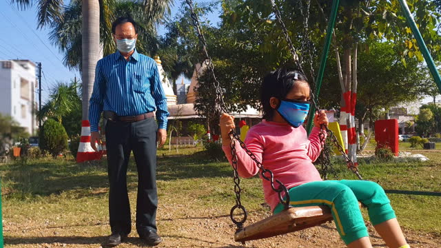 one indian senior man with a toddler girl kid enjoying swing ride wearing protective face mask in an empty public garden in a sunny day - india stock videos & royalty-free footage