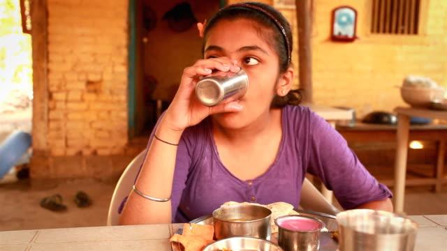 1 インド吸うティーンエイジャーの女の子は彼女の konkani 料理のお食事をお楽しみいただけます。 - 葉状体点の映像素材/bロール