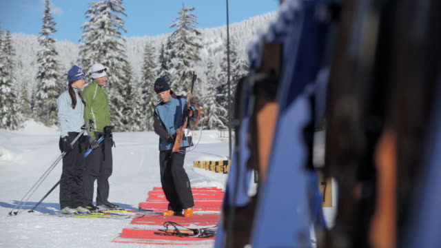 ms pan one instructor talking with couple in sunny winter day / whistler ,bc ,canada - biathlon stock videos and b-roll footage