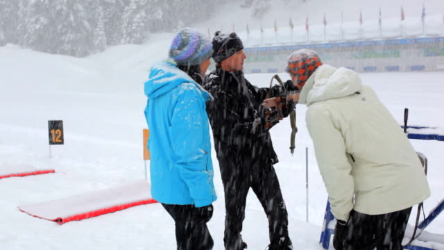 ms pan one instructor talking with couple / whistler ,bc ,canada - biathlon stock videos and b-roll footage
