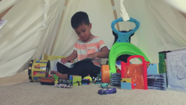One Kid With His Toys Scattered Around Sitting And Reading Book.
