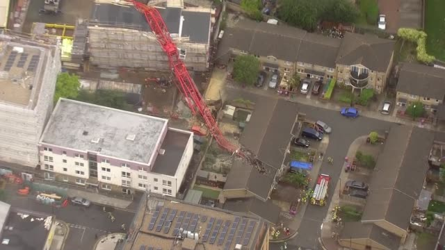 one killed and four injured following crane collapse in east london england london bow collapsed crane lying across construction site and crashed... - crane stock videos & royalty-free footage